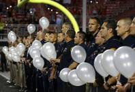 First responders hold 58 white balloons, representing the 58 victims of the Route 91 Harvest festival mass shooting, before a UNLV football game against San Diego State at Sam Boyd Stadium Saturday, Oct. 7, 2017.