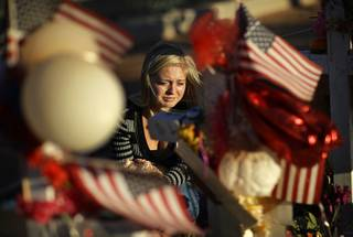 Alexandra Gurr cries as she lays flowers at a makeshift memorial for victims of a mass shooting Monday, Oct. 9, 2017, in Las Vegas. Stephen Paddock opened fire on an outdoor country music concert killing dozens and injuring hundreds.