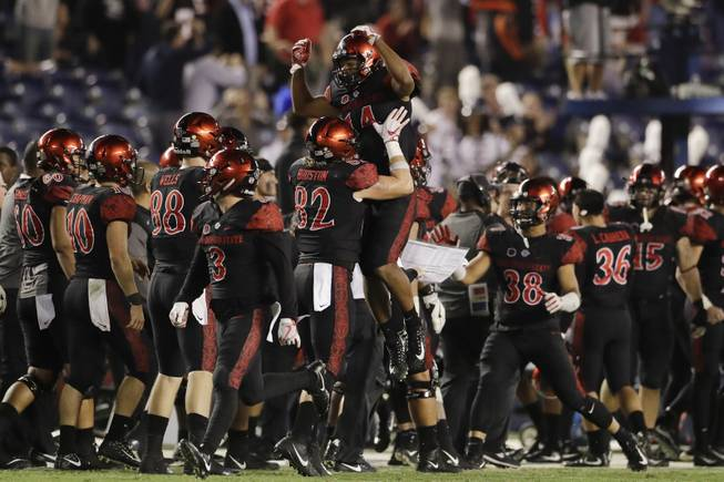San Diego State safety Tariq Thompson, above, celebrates with teammates after grabbing an interception during the second half of an NCAA college football game against Northern Illinois Saturday, Sept. 30, 2017, in San Diego. (