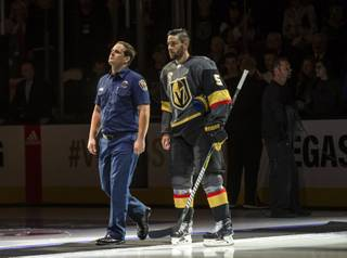 A first responder walks out onto the ice with Vegas Golden Knights defenseman Deryk Engelland (5) during opening ceremonies at their season home opener game at the T-Mobile Arena Tuesday, October 10, 2017.