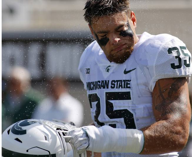 Michigan State linebacker Joe Bachie shakes off water as he warms up before an NCAA college football game against Western Michigan, Saturday, Sept. 9, 2017, in East Lansing, Mich.