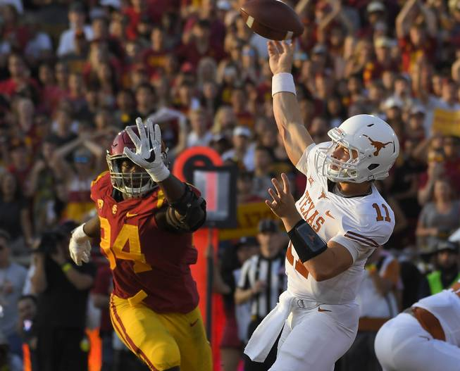 Texas quarterback Sam Ehlinger, right, passes as Southern California defensive tackle Rasheem Green defends during the first half of an NCAA college football game, Saturday, Sept. 16, 2017, in Los Angeles.