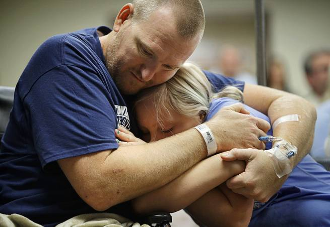 Las Vegas shooting victim Kurt Fowler embraces his 10-year-old daughter Timori Fowler during a country music performance at Sunrise Hospital, Wednesday, Oct. 11, 2017, in Las Vegas. Kurt Fowler was shot in the mass shooting at a music festival in Las Vegas.