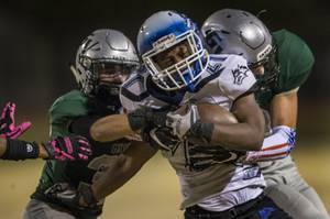 Basic's Dorian Ivan McAllister (21) is caught from behind by Green valley defenders in the Henderson Bowl high school football game Friday, October 13, 2017.