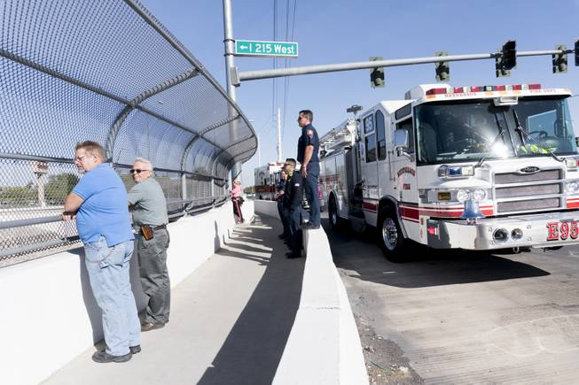 Firefighters from the Henderson E95 station wait on the I-215 Green Valley Pkwy overpass for fallen Officer Charleston Hartfield's motorcade to pass, Friday, Oct. 20, 2017.