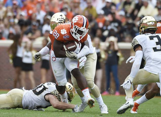 Clemson running back Tavien Feaster (28) runs for yardage against Wake Forest defensive players during the first half of an NCAA college football game, Saturday, Oct. 7, 2017, in Clemson, S.C. (AP Photo/Rainier Ehrhardt)