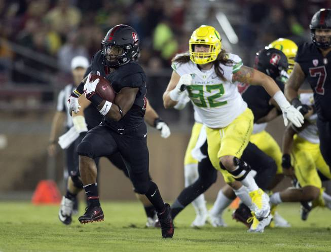 In this Oct. 14, 2017, file photo, Stanford's Bryce Love, left, breaks free for a long touchdown against Oregon during the first quarter of an NCAA college football game in Stanford, Calif. Love tweaked an ankle against Oregon and is a game-time decision for their game Thursday, Oct. 26, 2017, against Oregon State in Corvallis, Ore . (AP Photo/D. Ross Cameron, File)