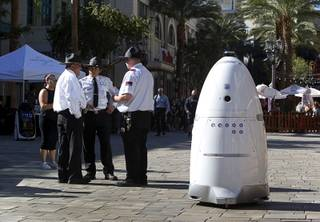 A Knightscope security robot travels past security officers  at the Linq Promenade Thursday, Nov. 9, 2017.