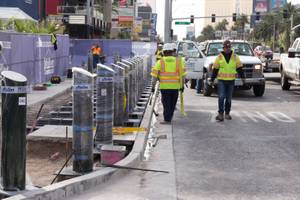 Construction workers install bollards along the Strip sidewalk in front ...