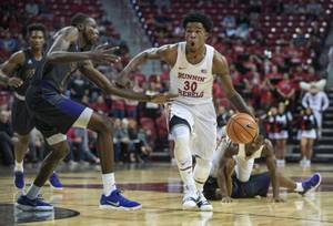 UNLV's guard Jovan Mooring (30) powers down the lane past Prairie View A&M's forward Keion Alexander (1) and teammates during their game at the Thomas & Mack Center on Wednesday, Nov. 15, 2017.