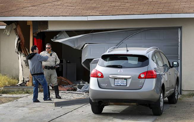 Resident Filipe Linares talks with a Metro Police office after a Ford Expedition SUV crashed into his home near Washington Avenue and Torrey Pines Drive Monday morning, Nov. 20, 2017.