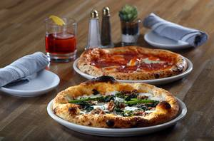 The Contento pizza, foreground, made with rapini (broccoli raab) bean puree, ricotta cheese, Mascarpone, and home-made sausage, at Contento Pizzeria & Bar inside Jerry Nugget, 1821 N Las Vegas Blvd, in North Las Vegas, Monday, Nov. 20, 2017. A Diavola pizza, rear, is made with spicy salami slices, spicy pepper sauce and mozzarella cheese.