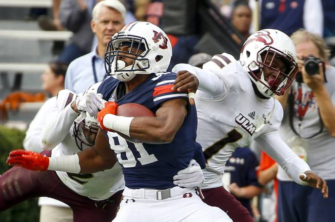 Auburn wide receiver Darius Slayton (81) is tackled by Louisiana Monroe safety Roland Jenkins (2) and cornerback Juwan Offray (1) after a reception in the first half of an NCAA college football game, Saturday, Nov. 18, 2017, in Auburn, Ala. (AP Photo/Butch Dill)
