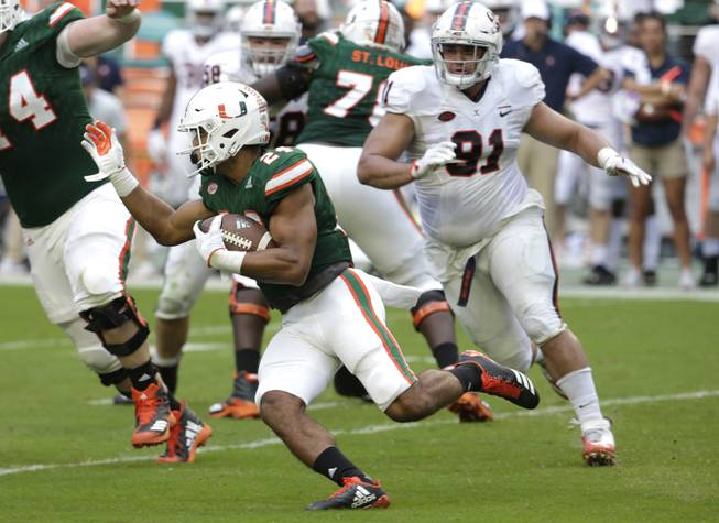 Miami running back Travis Homer 924) runs as Virginia defensive lineman Mandy Alonso (91) pursues during the second half of an NCAA college football game, Saturday, Nov. 18, 2017, in Miami Gardens, Fla. Miami won 44-28. (AP Photo/Lynne Sladky)