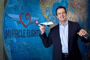Mark E. Brown, CEO of Miracle Flights, poses in the ...
