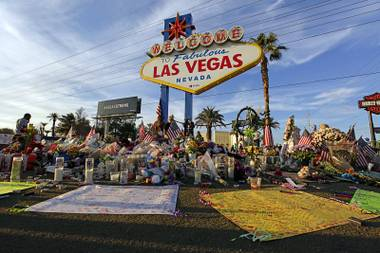 In this Monday, Oct. 16, 2017, photo, people visit a makeshift memorial for victims of the Oct. 1 mass shooting in Las Vegas.