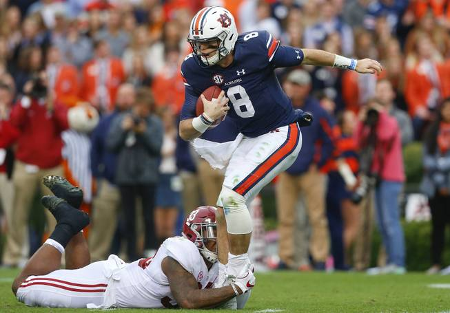Auburn quarterback Jarrett Stidham passes the ball against Alabama linebacker Anfernee Jennings during the first half of the Iron Bowl NCAA college football game, Saturday, Nov. 25, 2017, in Auburn, Ala.