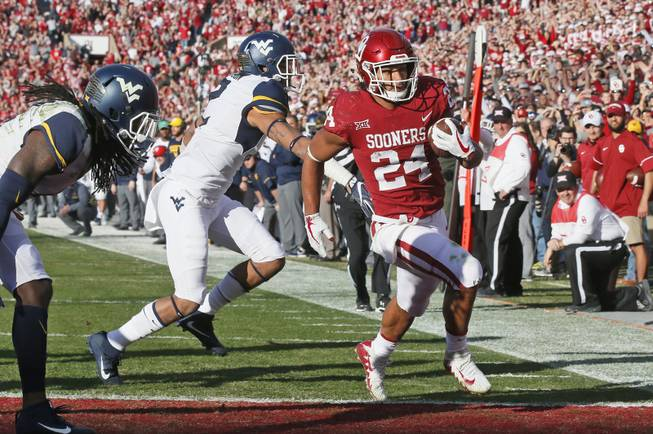 Oklahoma running back Rodney Anderson (24) scores in front of West Virginia safety Kenny Robinson (2) in the first quarter of an NCAA college football game in Norman, Okla., Saturday, Nov. 25, 2017.