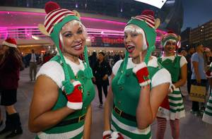 Santa's elves Cece Coreia, left, and Tala Marie pose before the second annual tree-lighting ceremony at Toshiba Plaza Thursday, Nov. 30, 2017. The