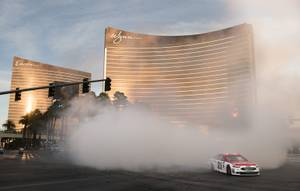 Ryan Blaney in the Wood Brothers Racing #21 Motorcraft Quicklane Ford exits a cloud of smoke after burning out at the NASCAR Victory Lap on the Las Vegas Strip at the intersection of Las Vegas Blvd. and Spring  Mountain Road on Wednesday, Nov. 29, 2017. CREDIT: Mark Damon/Las Vegas News Bureau