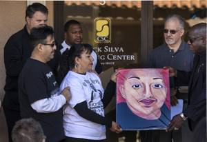 Angelica Cervantes with Miguel Cervantes receives a painting of her son Erick Silva fromBill Minson as Contemporary Services Corporation hosts a ceremony for the employee who lost his life while helping others at the Route 91 Harvest Music Festival on Friday, Dec. 1, 2017.   The painting is by artist Renee McDonnell.
