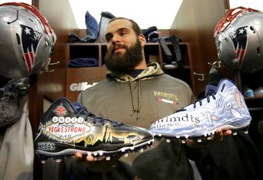 In this Wednesday, Nov. 29, 2017, photo, New England Patriots defensive end Lawrence Guy displays cleats that honor victims of the Oct. 1 Las Vegas shooting, left, and families who have lost an infant, right, in the team's locker room in Foxborough, Mass. Guy will honor both causes on the field this weekend during the NFL's My Cause, My Cleats initiative.