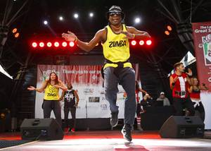 Zumba fitness instructor Jerry Johnson help warm up runners during ...
