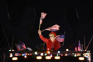 A woman waves United States flags during the Santa