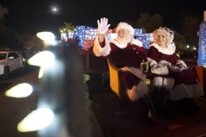 Santa and Mrs. Claus wave from their float during the ...