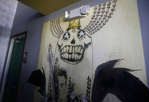 Artwork by artist/partner Jim Mahfood is displayed on a wall ...