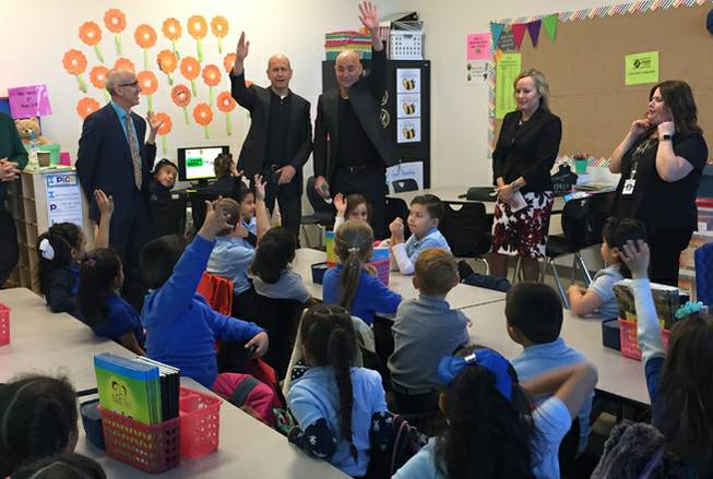 Andre Agassi, center right, and Bobby Turner, center left, of the Turner-Agassi Charter School Facilities Fund interact with first-graders Monday, Dec. 11, 2017, at Mater Bonanza Academy in Las Vegas. The charter school opened in August 2017.