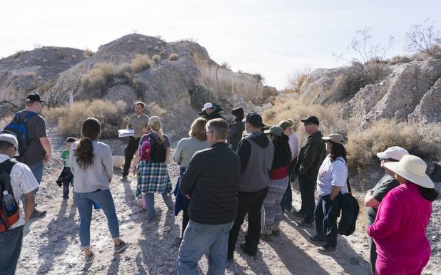 "Visitors listen to Park Ranger Garrett Fehner as he talks about an almost mile-long trench (seen in the background) that remains from a 1960's famous paleontology expedition called the ""Big Dig"" at Ice Age Fossils State ParkLas Vegas' newest state park where visitors can explore and learn about fossil beds located in the areaduring a ranger-guided hike, Monday, Jan. 1, 2018. With the park still in development, a visitor's center, interpretive trails and more infographic signs are expected to complete the park within two years."