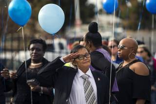 A friend and coworker salutes the casket during a recessional following a remembrance service for LaTosha Juane White at the Unity Baptist Church, she one of two security officers recently killed by a gunman at Arizona Charlie's on Saturday, Jan. 6, 2018.