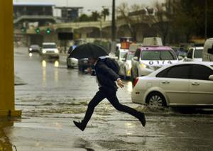 A pedestrian leaps over water onto the sidewalk along E. Elvis Presley Blvd. as rain soaks the Las Vegas valley on Tuesday, Jan. 9, 2018.