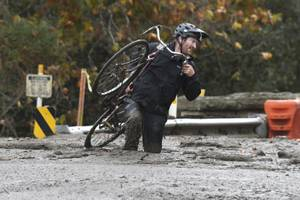 Carpinteria resident Jeff Gallup carries his bike through mud on Foothill Road in Carpinteria, Calif., Tuesday, Jan. 9, 2018. Homes were swept from their foundations as heavy rain sent mud and boulders sliding down hills stripped of vegetation by Southern California's recent wildfires. (AP Photo/Michael Owen Baker)