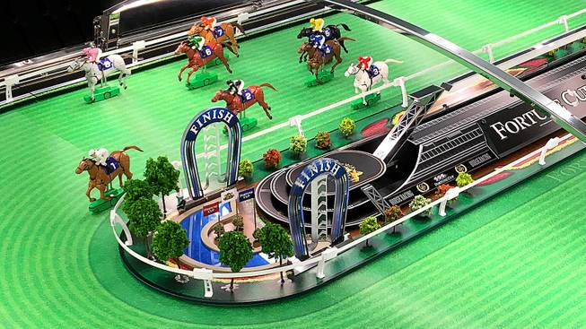 "The basic action of the Fortune Cup game is a series of tiny horse figurines ""racing"" around a track roughly the size of a foosball table."