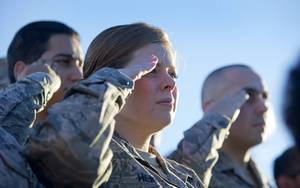 Airmen salute during the singing of the national anthem before ...