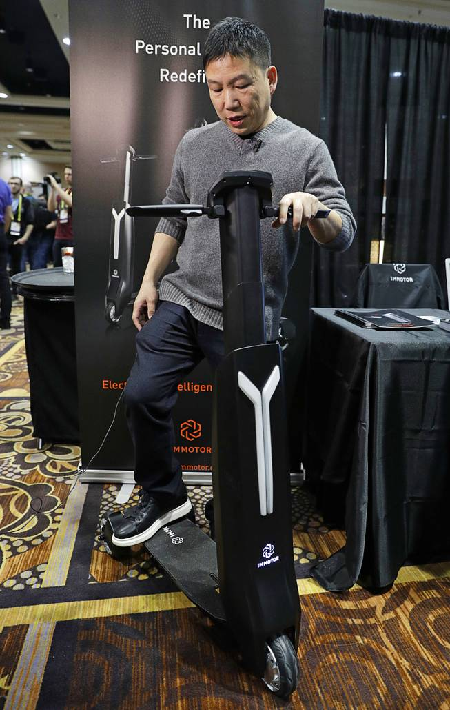 Daniel Huang demonstrates the Immotor Go during CES Unveiled before CES International, Tuesday, Jan. 3, 2017, in Las Vegas. The device is a battery powered foldable and portable smart vehicle.