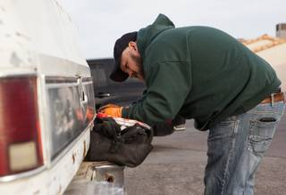 Volunteer Nicholas Marquart works on Kim Berlynn's truck during a free brake light repair clinic hosted by the Las Vegas Democratic Socialists of America at the First African Methodist Episcopal Church in North Las Vegas, Nev., on Saturday, Jan. 6, 2018.