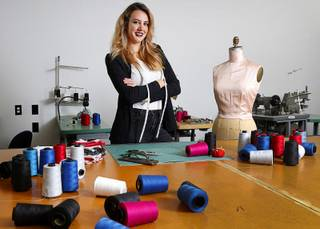 Ermelinda Manos, owner of Behind the Seams, a uniform and apparel design company, poses in a production room at the company Thursday, Jan. 18, 2018.