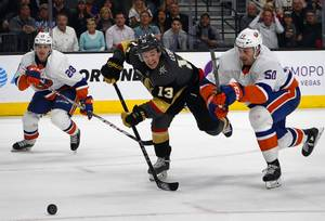 Golden Knights left wing Brendan Leipsic (13) chases after a puck with New York Islanders defenseman Sebastian Aho (28) and defenseman Adam Pelech (50) during the third period at T-Mobile Arena Thursday, Jan. 25, 2018.