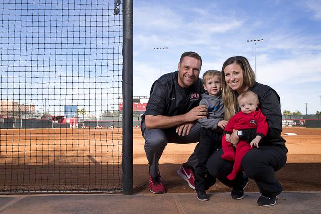 "UNLV head softball coach Kristie Fox-Jarvis poses with her son Mikie, 4 months, her husband and assistant coach Andy Jarvis and ""Little Andy,"" 2, in a dugout at the Eller Media Softball Stadium at UNLV Saturday, Jan. 27, 2018."