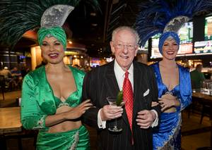 Former Las Vegas Mayor Oscar Goodman is accompanied by showgirls ...