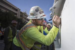 An iron worker signs the final steel beam that will ...