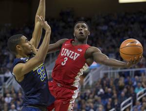 UNLV's Amauri Hardy shoots around Nevada's Josh Hall during the second half of an NCAA college basketball game in Reno, Nev., Wednesday, Feb. 7, 2018. (AP Photo/Tom R. Smedes)