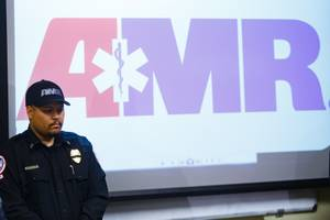 An AMR team member stands by during a press briefing Tuesday, Feb. 13, 2018 held to discuss details of an accident that caused the death of an AMR team member and a patient Monday night.
