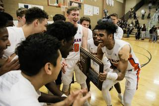 Bishop Gorman's Jamal Bey (35) holds the NIAA award and celebrates with his team after winning 57-46 against Clark during the Sunset Region Championship game at Legacy High School, Saturday, Feb. 17, 2018.
