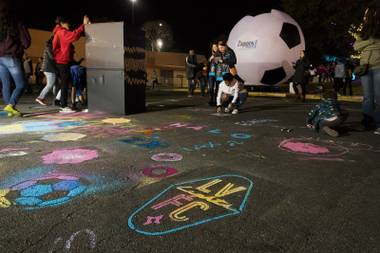 Kids draw on the asphalt during the tailgaite party prior to the Lights spring training match against the Vancouver Whitecaps Saturday, February 17, 2018 at Cashman Field.
