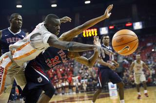 UNLV Rebels forward Cheikh Mbacke Diong (34) and Fresno State Bulldogs guard Deshon Taylor (21) chase after a loose ball during a game at the Thomas & Mack Center Wednesday, Feb. 21, 2018.