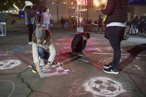 Young fans stencil designs in the parking lot before the ...